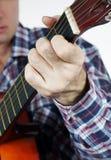 Mannen spelar ett ackord på gitarren Arkivfoto