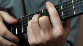 Mannen spelar gitarren, hans fingrar arkivfilmer
