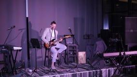 Mannen spelar gitarren på etapp lager videofilmer