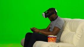 Mannen spelar leken i en VR-maskering med en styrspak grön skärm stock video