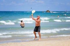 Mannen spelar Matkot i den medelhavs- stranden Royaltyfri Fotografi