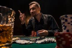 Mannen spelar poker med en cigarr och en whisky En man som segrar alla chiper på tabellen med tjock cigarettrök Royaltyfria Foton