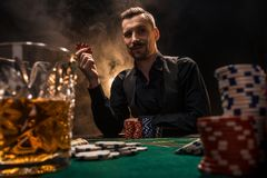 Mannen spelar poker med en cigarr och en whisky En man som segrar alla chiper på tabellen med tjock cigarettrök Arkivbild