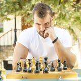 Mannen spelar schack. Arkivbild