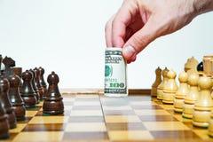 Mannen spelar schack med hundra dollar räkning arkivbild