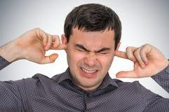 Mannen stänger öron med fingrar för att skydda från högt oväsen Royaltyfri Foto