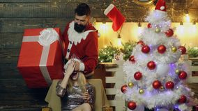 Mannen stänger flickans ögon med en hand och framlägger henne med en gåva Nytt års gåva för en älskvärd flicka Lynne för ` s för  arkivfilmer