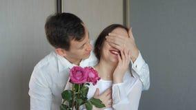 Mannen stänger hans är flickvännens ögon som gör överraskning och, ger rosor