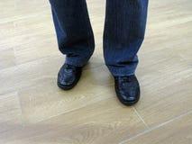 Mannen står i jeans och i tillfälliga skor Arkivfoton