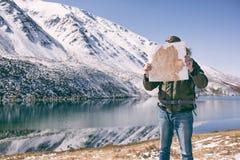 Mannen står mot ett berglandskap arkivbilder