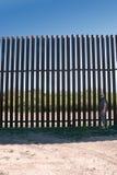 """Mannen står nära barriären en nya för järnMexico†""""Förenta staterna i bygden Texas royaltyfri bild"""