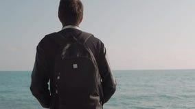 Mannen står nära havet med en ryggsäck på hans baksida och ser in i avståndet stock video
