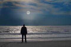 Mannen står på en ensam strand på moonrise Royaltyfri Fotografi