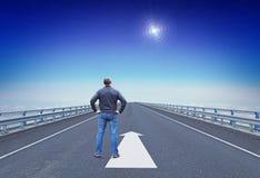 Mannen står på en huvudväg och ser på att vägleda stjärnan över horisont Royaltyfria Bilder