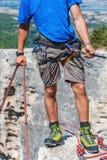 Mannen står på en klippa med repet Arkivbilder