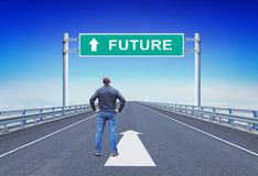 Mannen står på en motorway framme av vägmärket med textframtid Arkivfoto