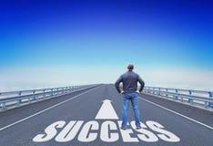 Mannen står på en väg som går till framgång Arkivfoto