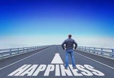 Mannen står på en väg som går till lycka Arkivbild