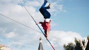 Mannen står på hans huvud på ett rep som sträcks ovanför jordningen Kalla skott av att utföra trick lager videofilmer