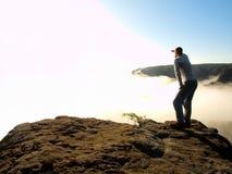 Mannen står på maximumet av sandsten vaggar i nationalparken Sachsen Schweiz och att hålla ögonen på över den dimmiga dalen för m Arkivbild