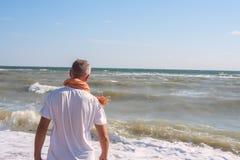 Mannen står på stranden i bränninglinje Royaltyfria Bilder