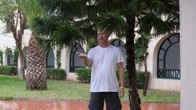 Mannen står under trädfilialer under regnsommardag, och lookig på hans gömma i handflatan på regndroppar arkivfilmer