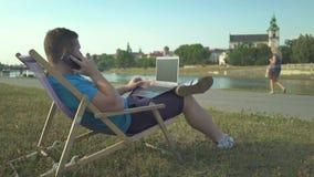 Mannen stannar till smartphonen och att bläddra bärbara datorn som ligger på sunbed av floden arkivfilmer