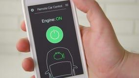 Mannen startar avlägset motorn av hans bil Bilfjärrkontroll genom att använda den uppdiktade manöverenheten för smartphoneapplika