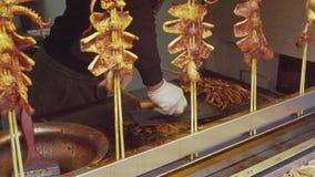 Mannen steker tioarmade bläckfisken asiatisk matgata Kryddig gatamat stock video