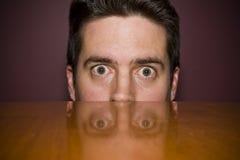 Mannen stirrar fearfully över en tabell arkivfoto