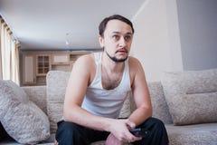 Mannen stirrar TV:N Fotografering för Bildbyråer