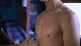 Mannen suddar en bröstkorg för grabb` s, för han startar att göra honom en tatuering arkivfilmer