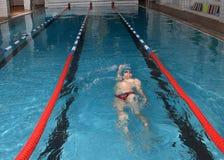 Mannen svävar på hans baksida i den inomhus offentliga simbassängen. Arkivfoton