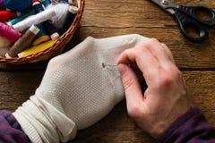 Mannen syr sockor på en träbakgrund Fotografering för Bildbyråer
