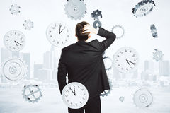 Mannen tänker om tiden som omges av klockan och kugghjul Arkivbilder