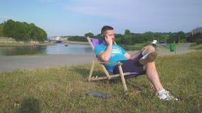 Mannen talar av smatphonen som ligger på sunbed av floden arkivfilmer