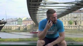 Mannen talar av smatphonen som sitter på bänken mot floden arkivfilmer