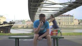 Mannen talar av smatphonen som sitter på bänken, pannaskottet stock video