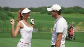 Mannen talar med kvinnan på golfen lager videofilmer