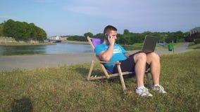 Mannen tallking vid smartphonen, bläddrar bärbara datorn och ligger på sunbed av floden Han är ung och har skägget Han är den ikl arkivfilmer