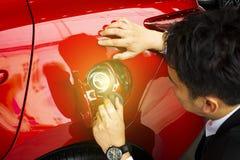 Mannen tankar med röd olja för bilmanpersonalen arkivbild