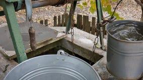 Mannen tappar kedjan med hinken in i lantligt väl för att dra vatten smutsigt vatten lager videofilmer