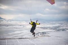 Mannen tar av med speedglideren från berget Royaltyfria Bilder