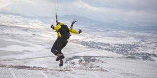 Mannen tar av med speedglideren från berget Royaltyfri Bild