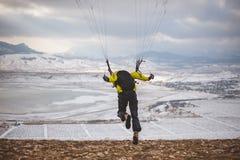 Mannen tar av med speedglideren från berget Arkivfoton