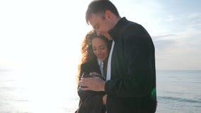 Mannen tar bilder av hans älskade flicka på kusten i vår Koppla ihop hållande ögonen på foto på kameran efter a lager videofilmer