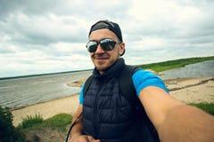 Mannen tar bilder av honom på bakgrunden av floden Royaltyfria Foton