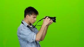 Mannen tar bilder av landskapen på den yrkesmässiga kameran grön skärm stock video
