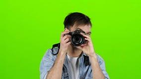 Mannen tar bilder av landskapen på den yrkesmässiga kameran grön skärm långsam rörelse stock video