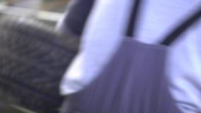 Mannen tar bort gummi från bilhjulet lager videofilmer